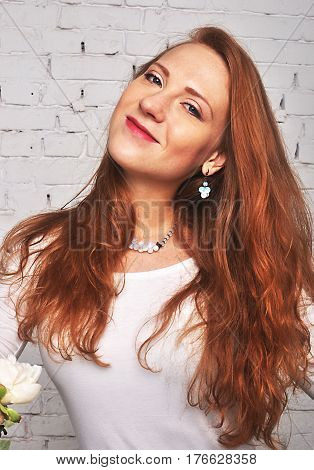 Beautiful red-haired girl smiling in white clothes and with jewelery