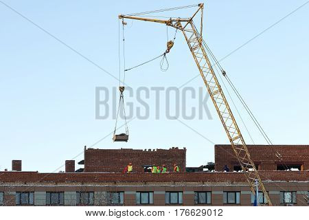 Tower crane and unidentified builders on the construction of building roof