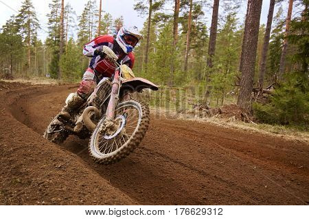 Motocross driver in action accelerating the motorbike after the corner on the race track.