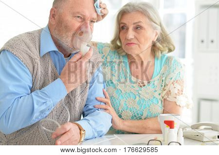Portrait of an elderly senior couple with oxygen mask