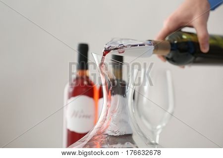 Sommelier pouring red wine into decanter