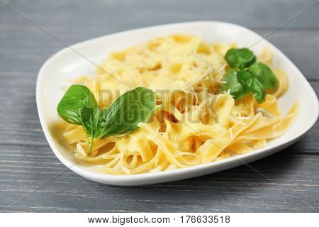 Portion of delicious pasta with cheese on wooden background