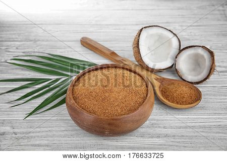 Bowl and spoon of brown sugar with coconut on wooden background