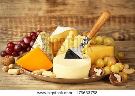 Tray with variety of cheese on wooden background