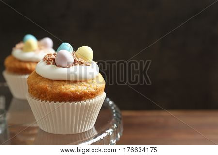 Decorated Easter cupcakes on glass cake stand against dark background