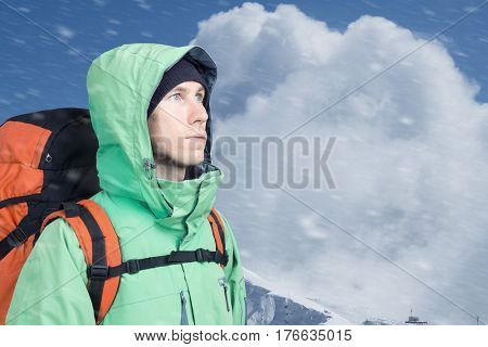 Man alpinist looks up against a winter mountain landscape.