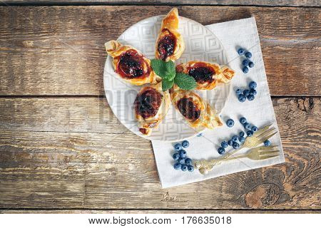 Sweet tasty pastries and fresh bilberries on wooden background, top view