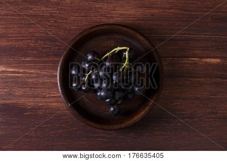 Dark grapes bunch. Ripe grape fruit on rustic plate. On wooden background.