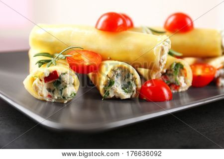 Delicious stuffed cannelloni with cherry tomatoes on rectangular plate