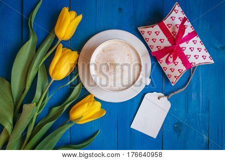Coffee mug with yellow tulip flowers and gift on blue rustic table from above, breakfast on Mothers day or Womens day .Spring  flowers bouquet
