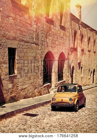 Small Italian car driving on medieval stone street vintage feeling
