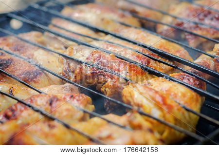 Grilled chicken legs and breasts. Rusty brazier.