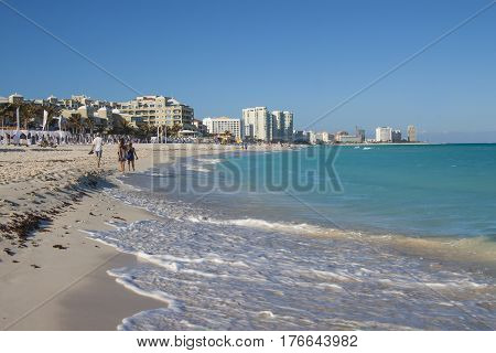 Cancun Mexico - February 25 2017: People relaxing along the sea shore on the Caribbean beach in the Area Hoteleria in Cancun Quintana Roo Mexico