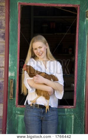 Blonde Teenage Woman Holding A Red Chicken