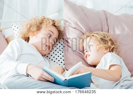 Boy Reading Book To Brother