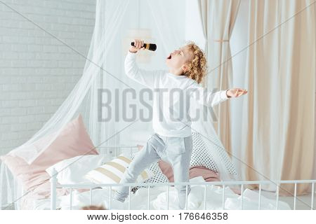 Boy Singing, Standing On Bed