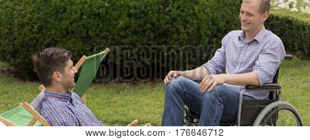 Disabled Man On Wheelchair Relaxing With Friend