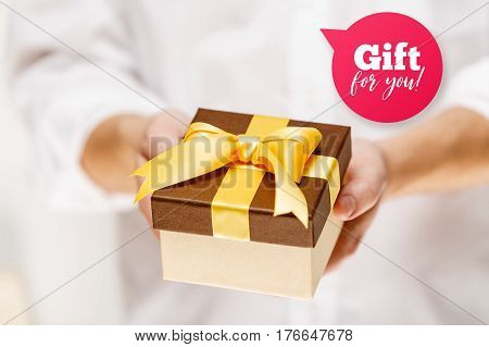 Male hands holding a gift box. Present wrapped with ribbon and bow. Gift for you speech bubble. Man in white shirt.