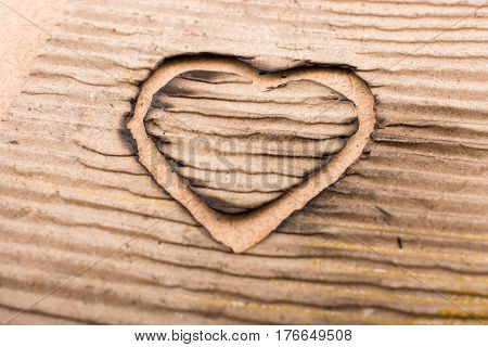 Heart shaped burnt out of a brown cardboard
