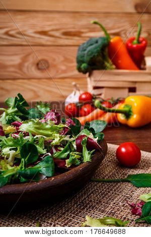 Provence salad. Leaves of endive or chicory, lamb and rose salad. Cherry tomato, pepper and brocoli. Raw vegetables. On wooden table.