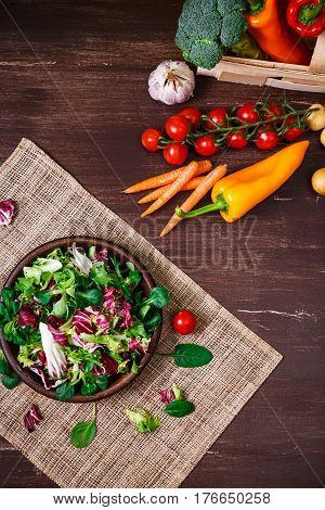 Provence salad. Leaves of endive or chicory, lamb and rose salad. Cherry tomatoes, pepper and carrot. Raw vegetables. On wooden table.