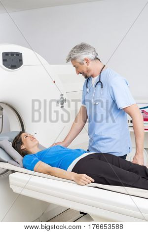 Doctor Talking To Patient Lying On CT Scan Machine