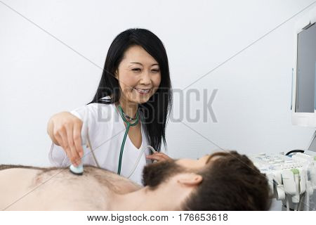Doctor Performing Ultrasound Treatment On Patient