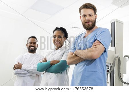 Smiling Radiologists Standing Arms Crossed In Examination Room