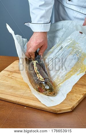 The cook wraps the fish in a paper for baking a collection of food recipes