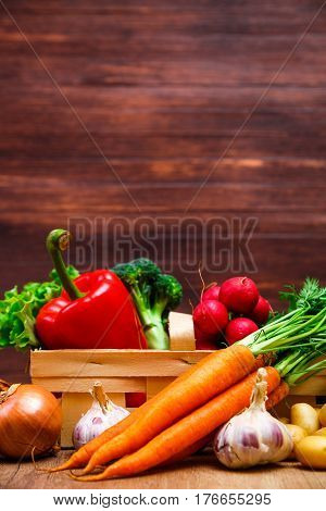 Vegetables. Potatoes, carrot and red pepper. Garlic and brocoli. Onion and radish. Wooden basket on rustic table.