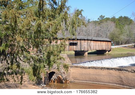Flowing waters beside wooden covered bridge at Watson Mill State Park in Comer, Georgia