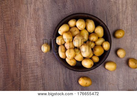 Potatoes in plate. Raw new potato. Fresh natural vegetables. Organic bio food on rustic wooden table.