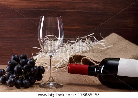 Bottle of red wine. Empty wineglass with dark grapes branch. On rustic wooden background.