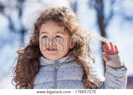 Beautiful Little sweet curly blond girl outdoor playing in the park 4 years old