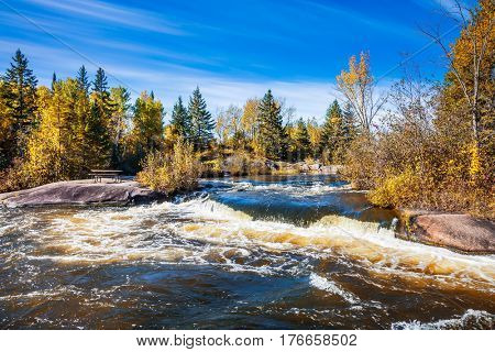 Autumn day. Foam water rapids on the smooth stones of the Winnipeg River. Old Pinawa Dam Provincial Heritage Park. The concept of ecological and adventure tourism