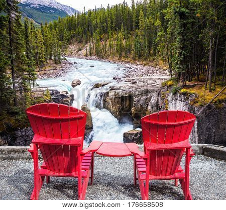 Two red deckchairs stand on the shore of the waterfall. Jasper National Park, Canada. The concept of extreme and ecological tourism