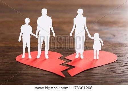 Close-up Of A Family Paper Cut On Broken Heart At Wooden Desk