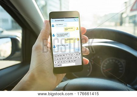 Close-up Of A Person Sending A Text Message Using Mobile Phone While Driving A Car