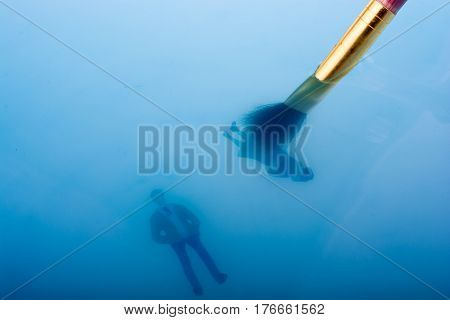 Brush And Little Floating Figurines In Water