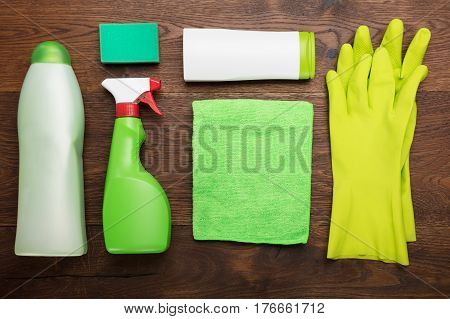 High Angle View Of A Cleaning Product And Tool On Wooden Desk