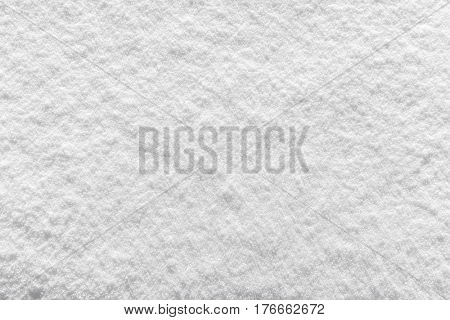 Background texture of fresh white winter snow viewed as a layer from above in a full frame view