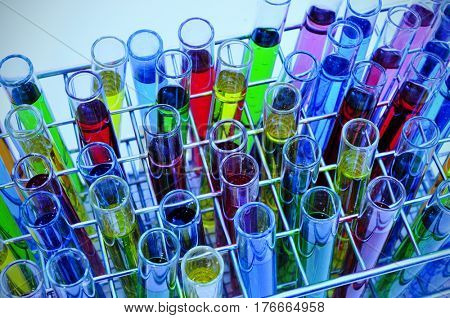 closeup of a pile of test tubes with liquids of different colors, in a laboratory