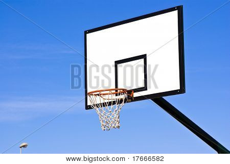 a basketball ring over a sunny blue sky
