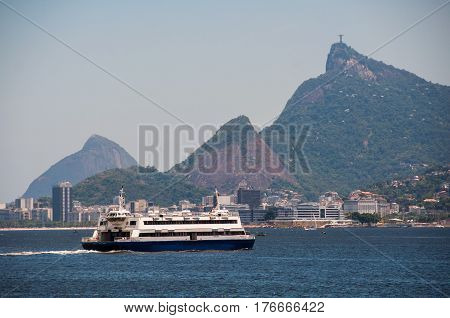 Rio de Janeiro, Brazil - February 11, 2017: Ferry boat crossing Guanabara bay with Corcovado in background. erries are useful mode of transport for getting between Rio de Janeiro and Niteroi.