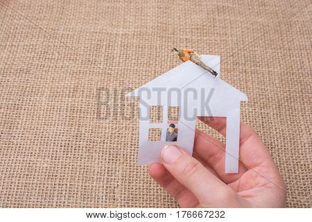 Paper house and a man figurine on a linen canvas background