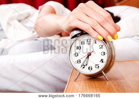 Woman turning off her alarm clock in her bedroom