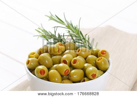 bowl of green olives stuffed with red pepper - close up