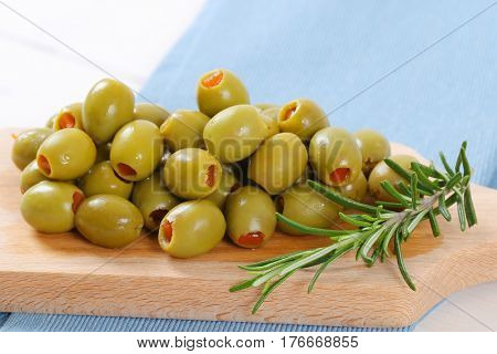 pile of green olives stuffed with red pepper on wooden cutting board - close up