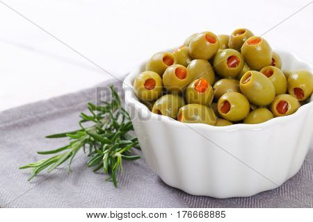 bowl of green olives stuffed with red pepper on grey place mat - close up