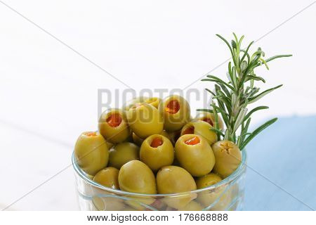 glass of green olives stuffed with red pepper - close up
